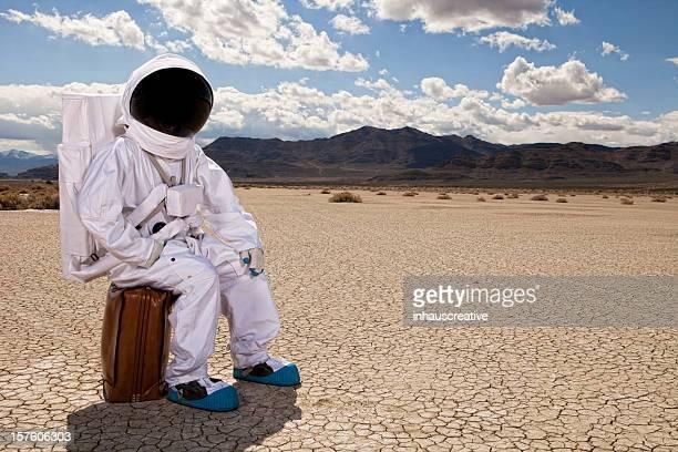 Astronaute, assis sur la valise dans le désert