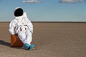 Astronaut sitting on suitcase