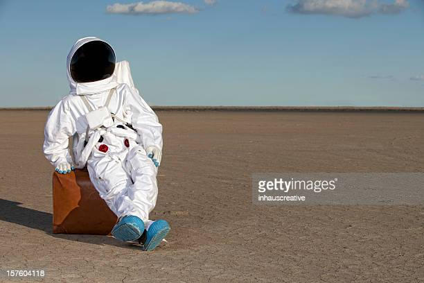 Astronaut sitting on suitcase