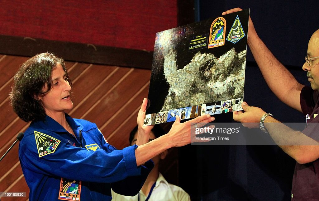 Astronaut Sunita L Williams displaying a photograph of her mission to Moon during an interaction with School children organised by the National Science Centre on April 1, 2013 in New Delhi, India.