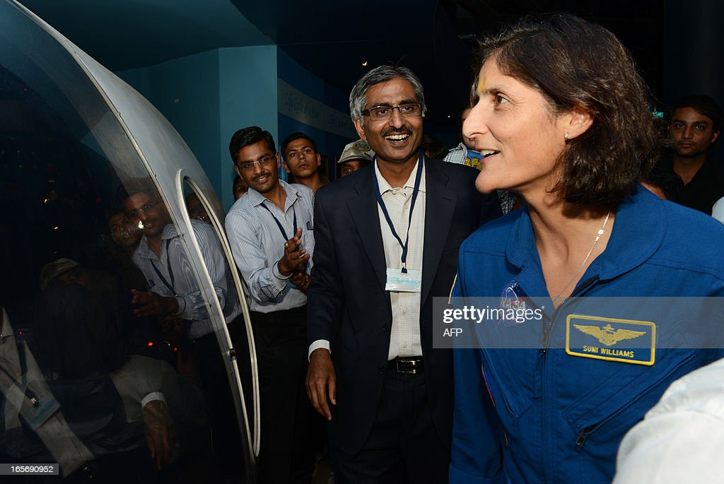 US astronaut Sunita Williams (R) admires a model of a space ship during her visit at the Gujarat Science City on the outskirts of Ahmedabad on April 5, 2013. Williams holds a world record for total cumulative spacewalk time by a female astronaut and has spent a total of 322 days in space on two missions. AFP PHOTO / Sam PANTHAKY