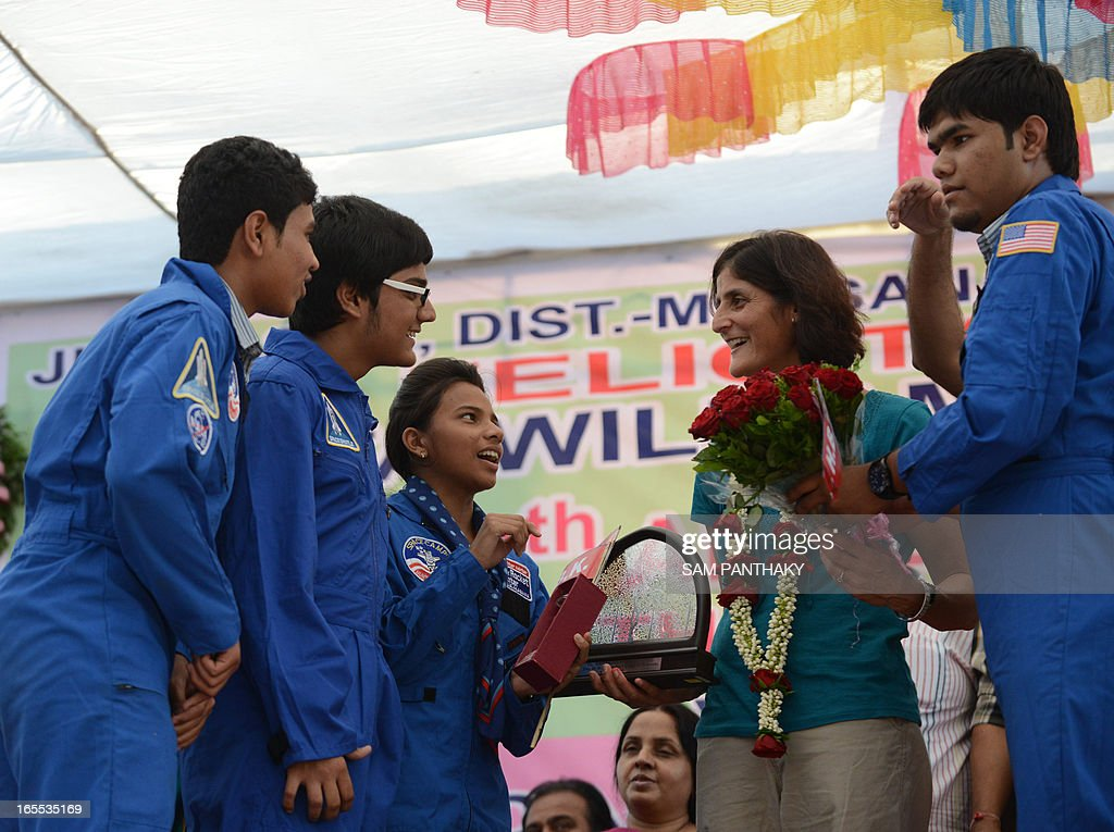 US astronaut Sunita Williams (2R) interacts with students, who had participated in NASA Space Camp, after she arrived at the Dola Mataji Temple, at Jhulasan Village, where she was born, some 50 kms from Ahmedabad on April 4, 2013. Williams holds a world record for total cumulative spacewalk time by a female astronaut and has spent a total of 322 days in space on two missions. AFP PHOTO / Sam PANTHAKY