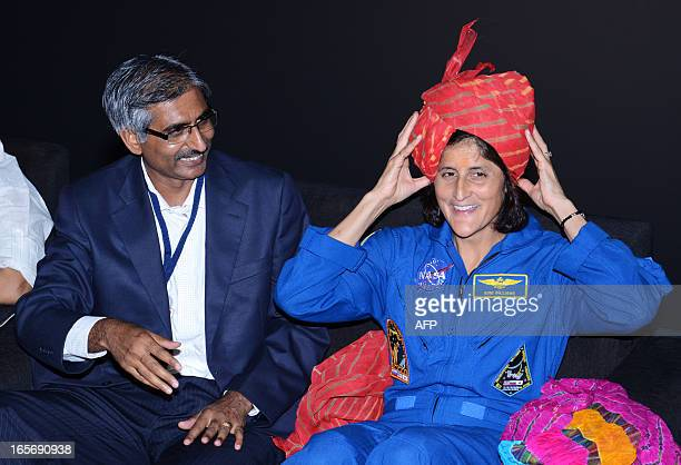 US astronaut Sunita Williams reacts as she removes a a traditional turban during her visit at the Gujarat Science City on the outskirts of Ahmedabad...