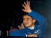 Astronaut Takuya Onishi of the Japan Aerospace Exploration Agency waves to his relatives from a bus after his space suit was tested at the...