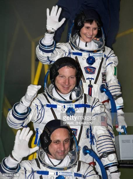 US astronaut Terry Virts Russian cosmonaut Anton Shkaplerov and European Space Agency's Italian astronaut Samantha Cristoforetti wave as they board...