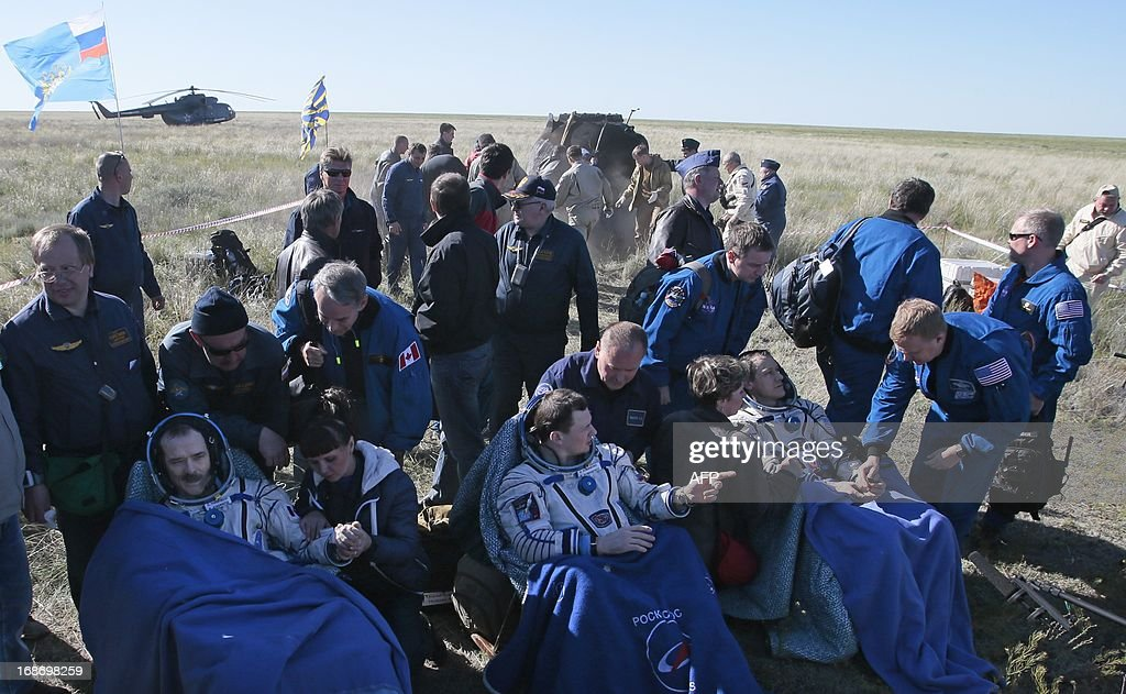 US astronaut Thomas Marshburn Russian cosmonaut Roman Romanenko and Canadian astronaut Chris Hadfield rest shortly after the landing aboard the...