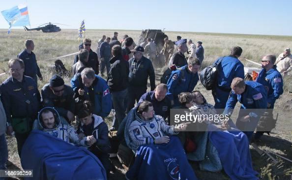 US astronaut Thomas Marshburn Russian cosmonaut Roman Romanenko and Canadian astronaut Chris Hadfield rest shortly after the landing aboard the...