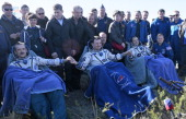 US astronaut Thomas Marshburn Russian cosmonaut Roman Romanenko and Canadian astronaut Chris Hadfield join their hands as they rest shortly after the...