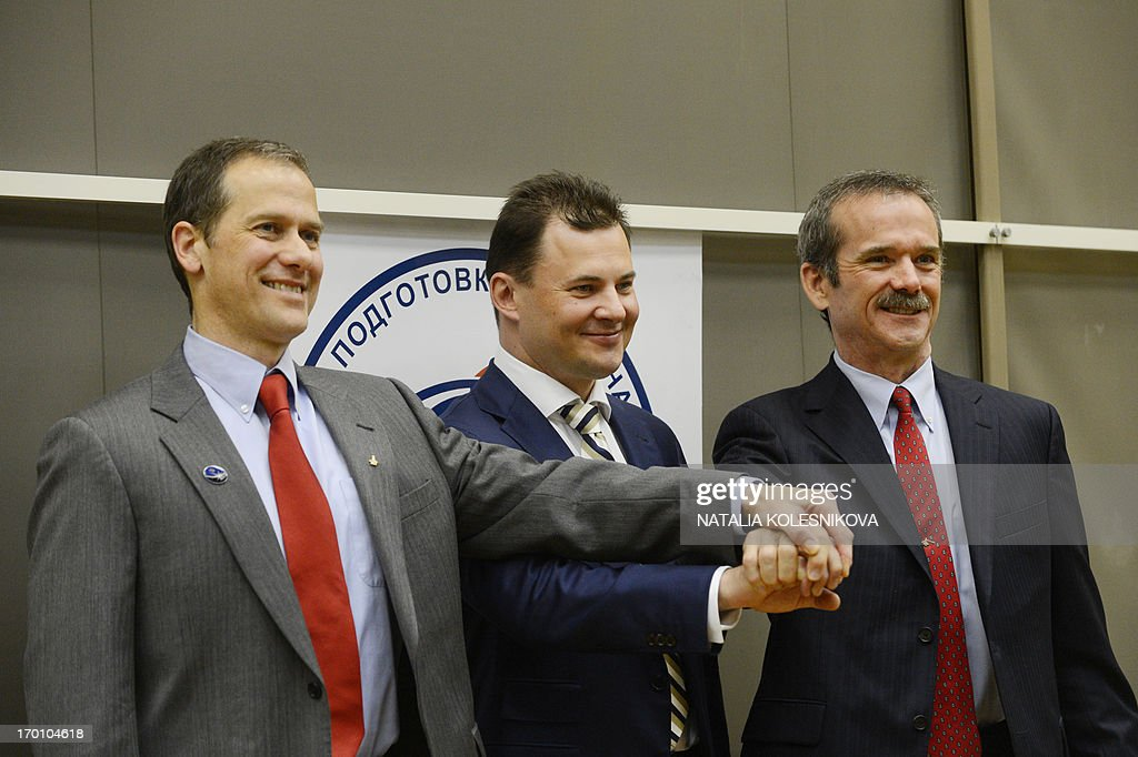 US astronaut Thomas Marshburn Russian cosmonaut Roman Romanenko and Canadian astronaut Chris Hadfield join their hands as they attend a press...