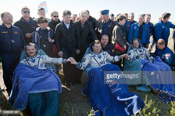 US astronaut Tom Marshburn Canadian spaceman Chris Hadfield and Russian cosmonaut Roman Romanenko join their hands as they rest shortly after the...
