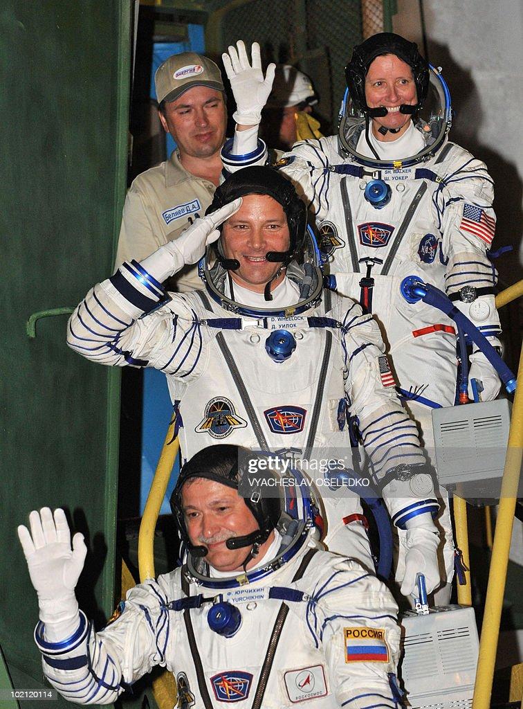 US astronauts Doug Wheelock (C), Shannon Walker (Top) and Russian cosmonaut Fyodor Yurchikhin (front) wave while boarding a Russian Soyuz TMA-19 rocket at Kazakhstan's Russian-leased Baikonur cosmodrome on June 15, 2010.