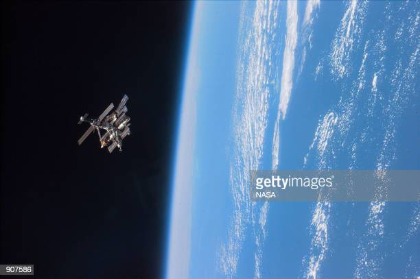 STS79 astronauts enjoy this view of the Mir complex backdropped against the blackness of space over Earth's horizon A thin blue line of airglow runs...