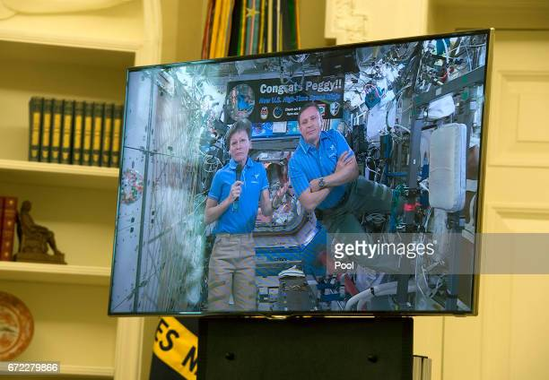NASA Astronauts Peggy Whitson and Jack Fischer appear on a video screen as President Donald Trump hosts a video conference with them aboard the...
