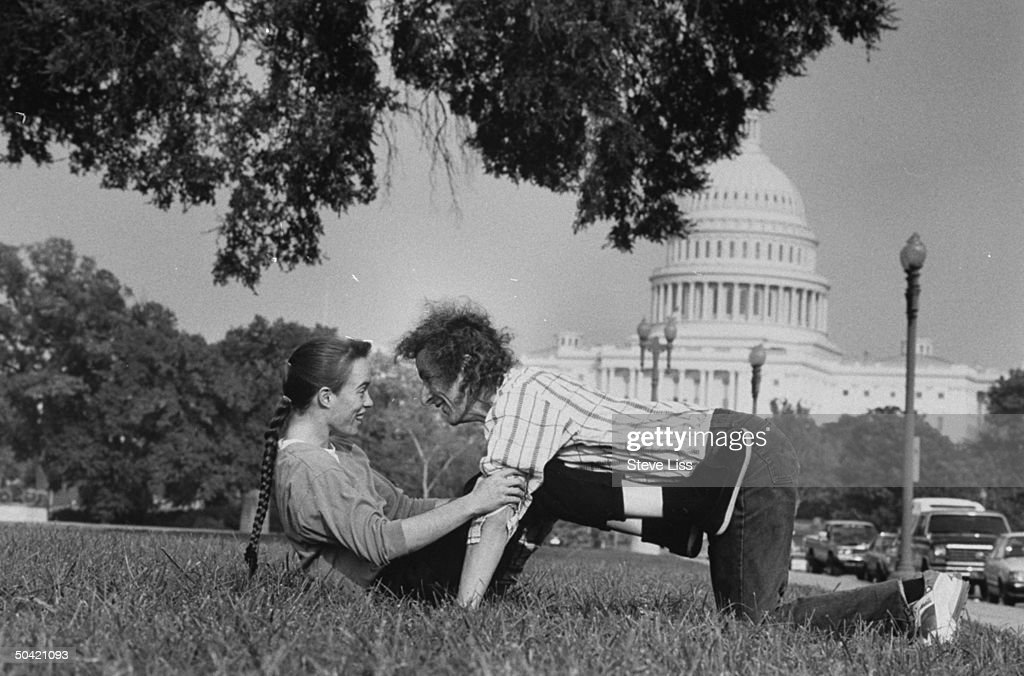 Astronomer/computer mgr. Cliff Stoll posing playfully w. his wife Martha Matthews in park in front of US Capitol bldg.