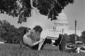 Astronomer/computer mgr Cliff Stoll posing playfully w his wife Martha Matthews in park in front of US Capitol bldg