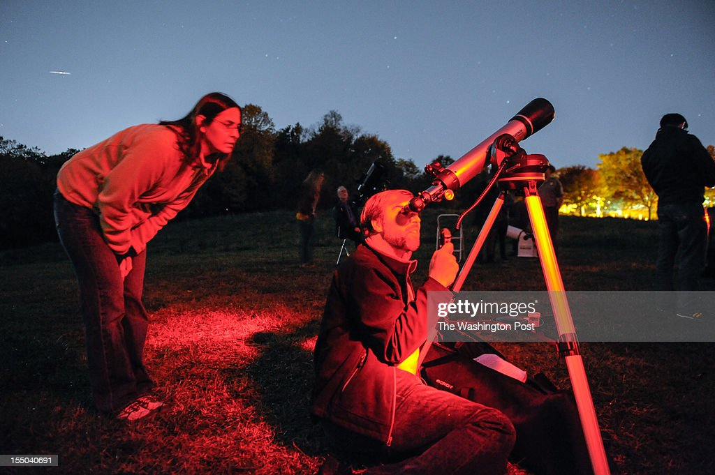 Astronomy enthusiast Stephen Tibbets calibrates his telescope as his wife Kathy looks on during the National Capital Astronomers Club monthly outreach event at Rock Creek Park in Northwest Washington. October, 20, 2012 in Washington, DC.