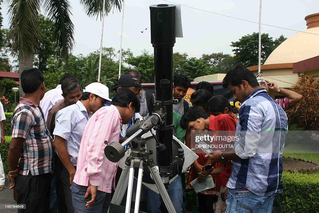 Astronomy enthusiasts watch the transit of Planet Venus across the Sun with use of a telescope in Siliguri on June 6, 2012. Astronomers around the world trained their telescopes on the skies to watch Venus pass in front of the Sun, a once-in-a-lifetime event that will not be seen for another 105 years. AFP PHOTO/Diptendu DUTTA
