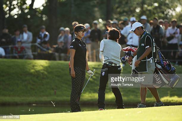 Asuka Kashiwabara of Japan checks rules with a tournament official after hitting the ball into the water onthe 17th hole during the final round of...