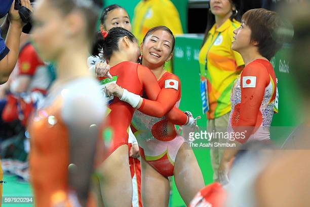 Asuka Teramoto of Japan is embraced by her team mates after competing on the uneven bars of the Artistic Gymnastics Women's Team Final on Day 4 of...