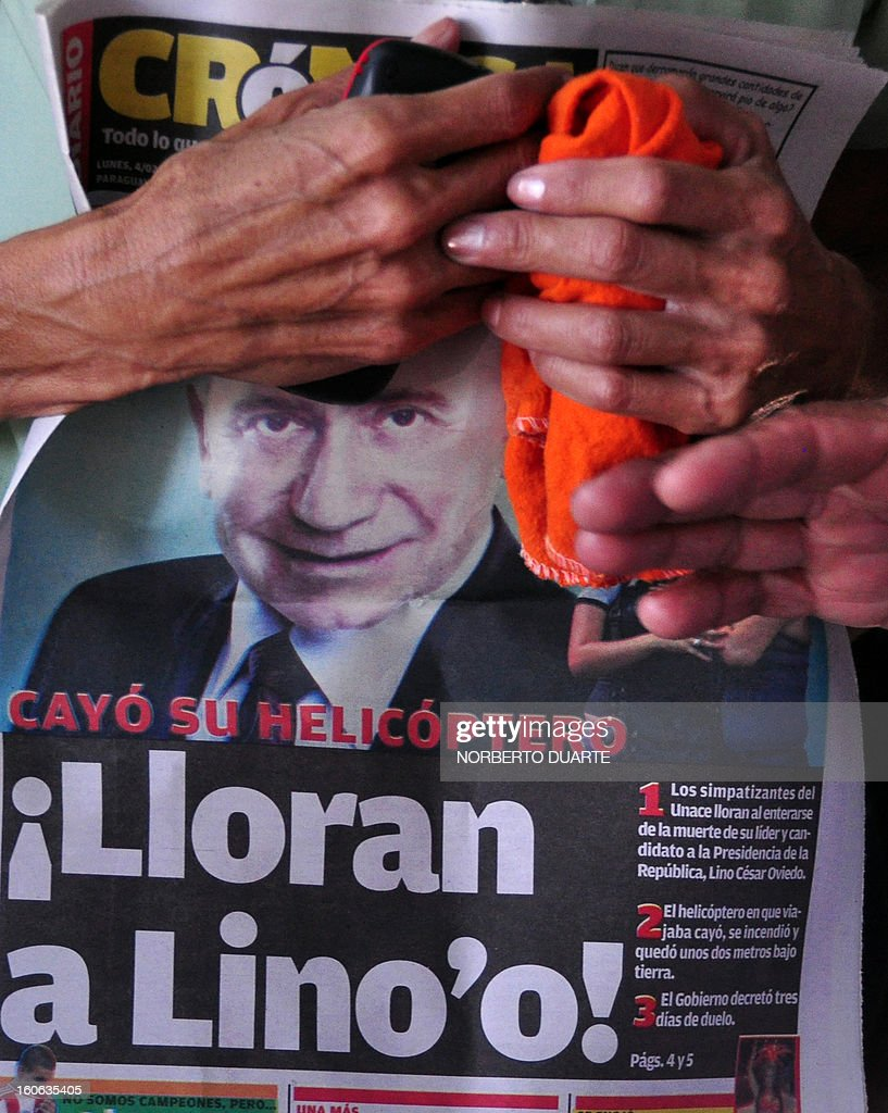 Asupporter of former Paraguayan general and UNACE party presidential candidate Lino Oviedo --who died along with his bodyguard Denis Galeano and pilot Ramon Picco Delmas in a helicopter crash on February 2-- holds a newspaper with a picture of him, at the party's headquarters in Asuncion on February 4, 2013. Oviedo, 69, the controversial presidential candidate who helped topple Paraguayan dictator Alfredo Stroessner in 1989, died when the aircraft crashed en route to Asuncion while returning from a campaign rally in northern Paraguay, prompting claims of foul play. AFP PHOTO/Norberto DUARTE