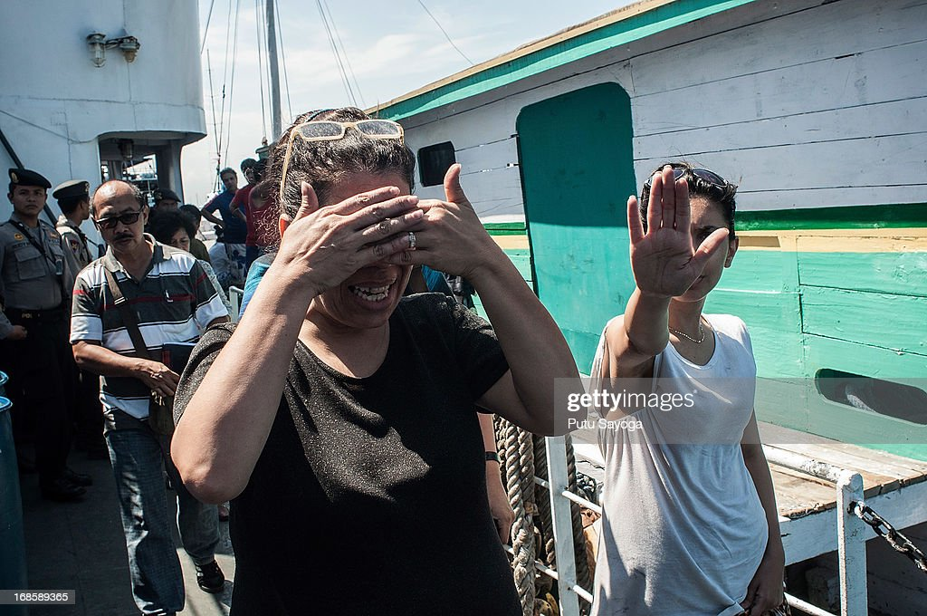 Asylum seekers cover their face from being photographed as they leave a boat on May 12, 2013 in Bali, Indonesia. Indonesian police have intercepted an asylum seeker boat harboured in Bali that was believed to be heading to Australia. 80 to 100 people of Middle Eastern origin where found in the hull of a wooden boat on Benoa Harbour.