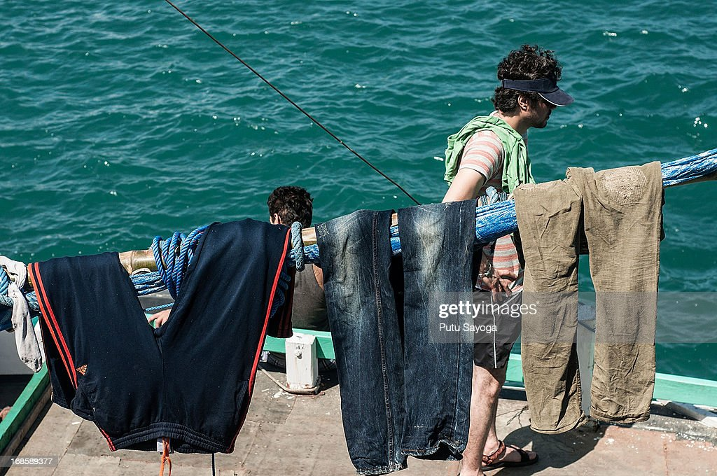 Asylum seekers dry their pants on a boat on May 12, 2013 in Bali, Indonesia. Indonesian police have intercepted an asylum seeker boat harboured in Bali that was believed to be heading to Australia. 80 to 100 people of Middle Eastern origin where found in the hull of a wooden boat on Benoa Harbour.