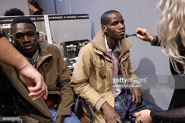 Asylum seekers get their makeup done backstage prior to taking part in the special event 'Generation Africa' during the ITC Ethical Fashion...