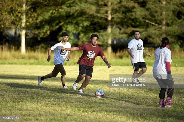 Asylum seekers in a refugee center in Hennala Lahti Finland on September 30 2015 and locals play football together during the 'Let's play ball...