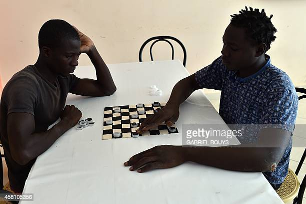 Asylum seekers play draughts at the hotel Villa Mokarta temporarily transformed in a center for immigrants on October 21 2014 in Salemi near Trapani...