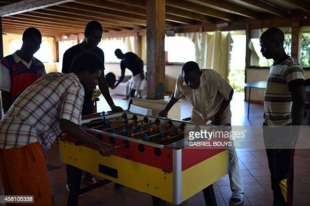 IDE Asylum seekers play table football at the hotel Villa Mokarta temporarily transformed in a center for immigrants on October 21 2014 in Salemi...