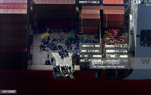 Asylum seekers prepare to be transferred by special forces' semi inflatable boats bottom right between the Norwegian freighter MV Tampa and HMAS...