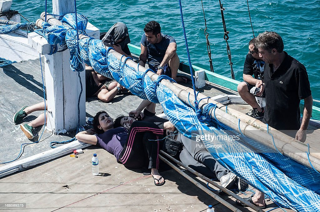 Asylum seekers refuse to leave the boat on May 12, 2013 in Bali, Indonesia. Indonesian police have intercepted an asylum seeker boat harboured in Bali that was believed to be heading to Australia. 80 to 100 people of Middle Eastern origin where found in the hull of a wooden boat on Benoa Harbour.
