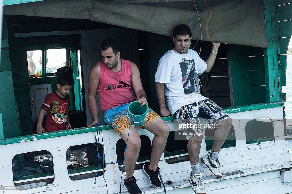 Asylum seekers sit on the back of a boat on May 12, 2013 in Bali, Indonesia. Indonesian police have intercepted an asylum seeker boat harboured in Bali that was believed to be heading to Australia. 80 to 100 people of Middle Eastern origin where found in the hull of a wooden boat on Benoa Harbour.