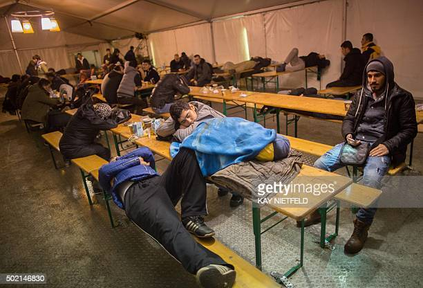 Asylum seekers sleep in a tent as they wait to register at the State Office of Health and Social Affairs registration centre in Berlin on December 21...
