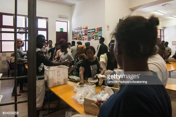 Asylum seekers take their lunch provided by staff the Hub centre feed nearly 1000 asylum seekers per day on July 27 2017 in Bologna Italy In an...