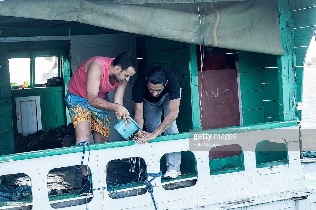 Asylum seekers use sea water to wash their hands on May 12, 2013 in Bali, Indonesia. Indonesian police have intercepted an asylum seeker boat harboured in Bali that was believed to be heading to Australia. 80 to 100 people of Middle Eastern origin where found in the hull of a wooden boat on Benoa Harbour.