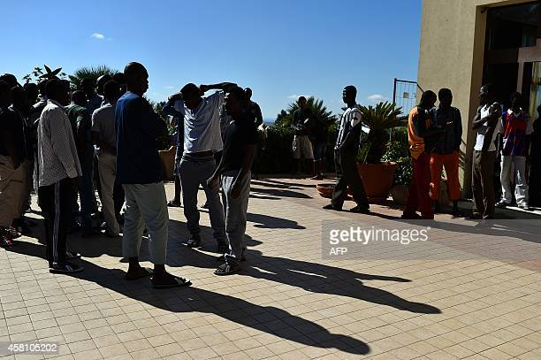 Asylum seekers wait at the hotel Villa Mokarta temporarily transformed in a center for immigrants on October 21 2014 in Salemi near Trapani in Sicily...
