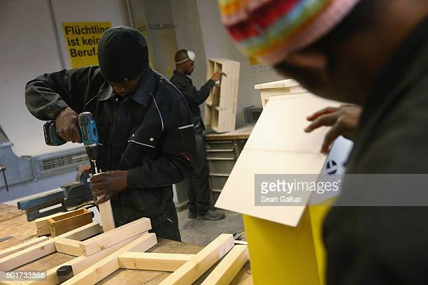 Asylumapplicants from Africa participate in the cabinetmaking tradecrafts exposure program at the Arrivo center on December 17 2015 in Berlin Germany...