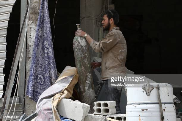 ASyrian man inspects wreckage of collapsed Arbin hospital after Assad Regime's airstrike hit residential areas at the Arbin district of Eastern...