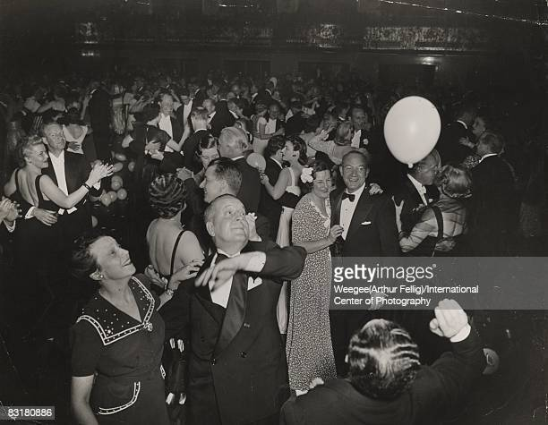 At a ball held at the WaldorfAstoria hotel in Manhattan men and women dance on the floor while in the foreground two men prepare to hit a balloon...