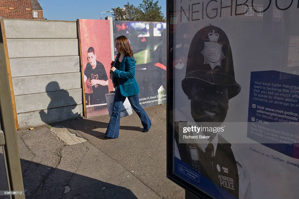 At a bus stop on the Leyton Road a poster ad for community policing showing a black police officer in housing estate opposite 2012 Olympic site...