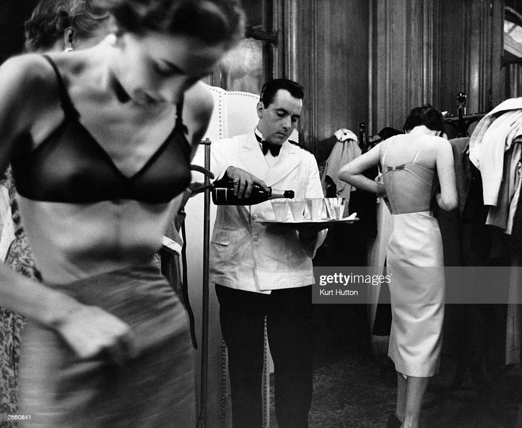 At a fashion show in France, John Cavanagh's models change backstage as a waiter pours champagne. Original Publication: Picture Post - 6434 - British Girls Storm Paris - pub 1953