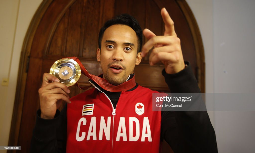 At a heart felt ceremony at King Edward Elementary School in Kitchener this morning, selfless Canadian Olympian Gilmore Junio was awarded a one-of-a-kind commemorative medal to honour his personal sacrifice when he gave up his spot in the Men's 1000m Speed Skating event at the Sochi Olympics to teammate Denny Morrison who went on to capture an Olympic Silver Medal for Canada. The team at Jacknife Design were inspired by Gilmore's selfless act and gave him a commemorative medal that was designed by them and funded with help from everyday Canadians. Gilmore is at the Jacknife offices in these photos showing off his medal in Toronto, May 14, 2014.