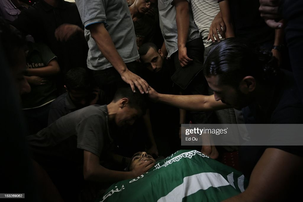 At a mosque in Gaza City, relatives huddle over the body of Palestinian militant Zakareya al-Jammal, 21, who was killed by Israeli fire as he was preparing to launch rockets into Israel on Sept. 6, 2012. He was the son of prominent Hamas commander Abu Zakaria al-Jamal, who was killed during Israel's Operation Cast Lead.