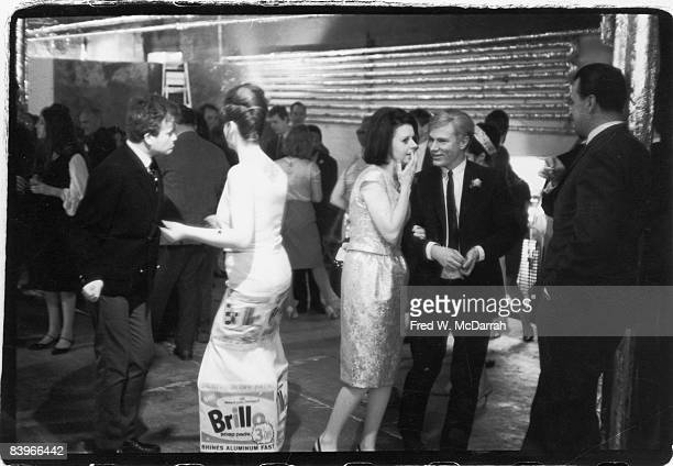 At a party at the his studio the Factory American pop artist Andy Warhol listens as Margarette Lampkin whispers in his ear while next to them...