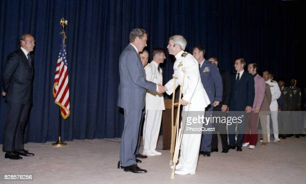 At a predinner reception US President Richard Nixon shakes hands greets former North Vietnamese prisoner of war Captain John McCain Washington DC May...