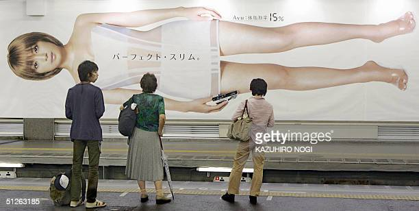 At a railway station terminal in Tokyo passengers look at a huge billboard showing Japanese star singer Ayumi Hamasaki with sexy seethrough onepiece...