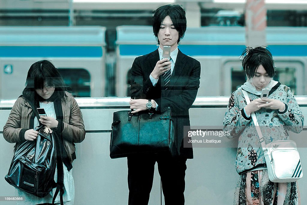 CONTENT] At a train station in Tokyo, Japan, three young Japanese adults check their cell phones while waiting for the train. Original description on Flickr comments on how technology has connected more people than ever before on social networks, but discourages them from everyday social interactions in real life
