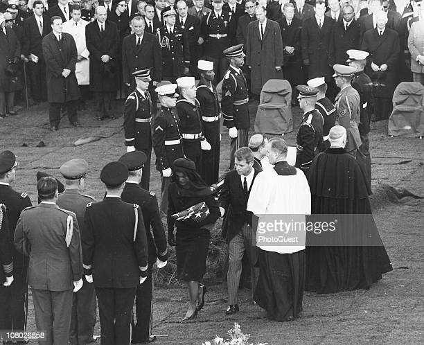 At Arlington National Cemetary Jacqueline Kennedy accompanied by her brotherinlaw Robert F Kennedy carries a folded flag away from the gravesite of...