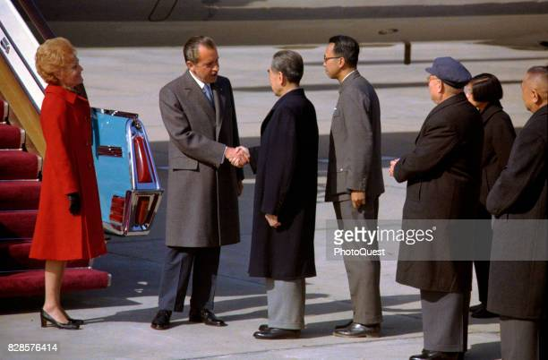 At at the foot of Air Force One's airstair US President Richard Nixon shakes hands with Premier of the People's Republic of China EnLai Chou as First...
